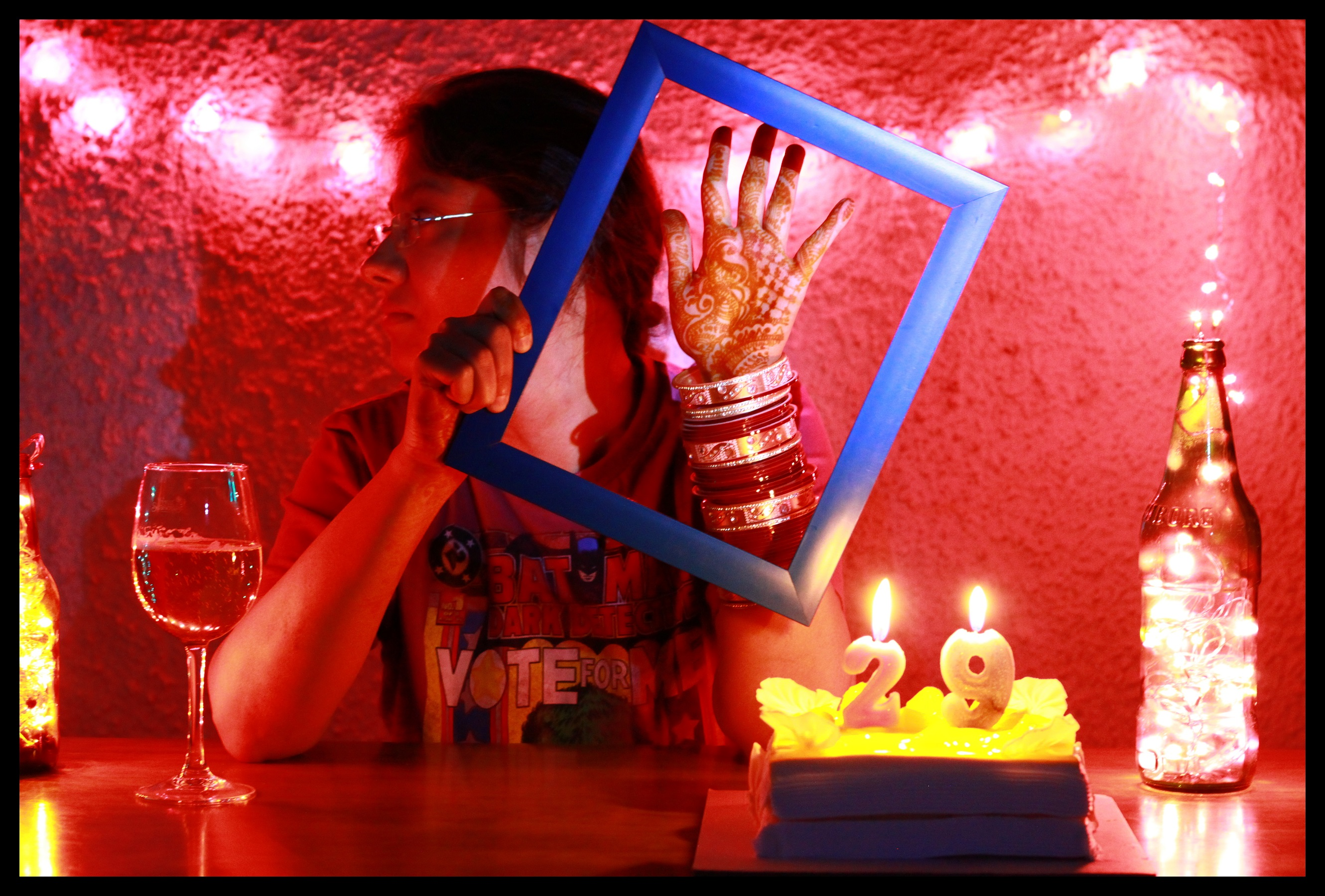 A person with dark hair and glasses holds up a blue picture frame to display the mehendi on their hand and the chura on their wrist. A birthday cake with the number 29 is to the right, and a wine glass is to the left. The person's head is turned to the side; the backdrop is a red wall.