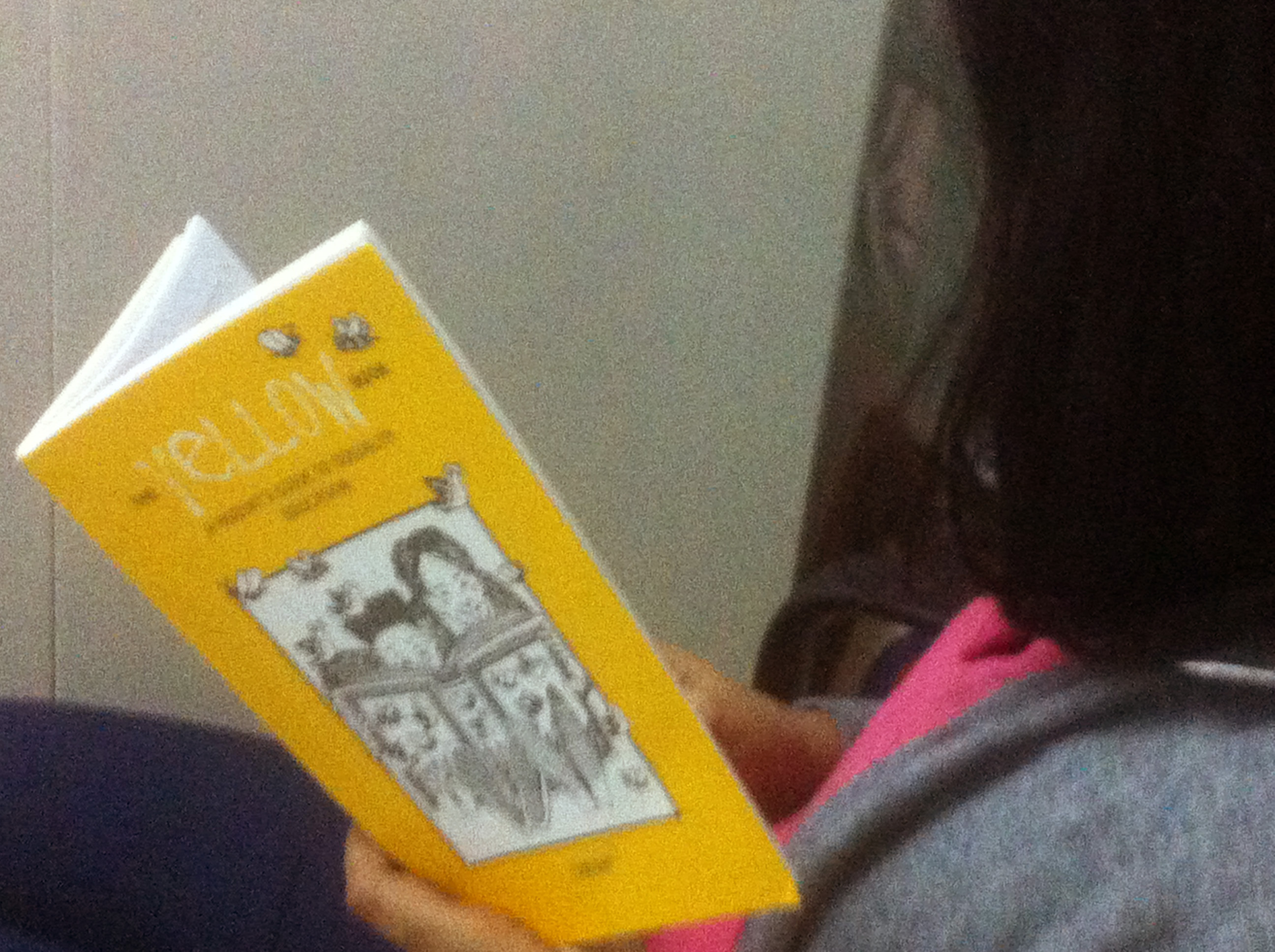 A person with short dark hair reads TARSHI's The Yellow Book