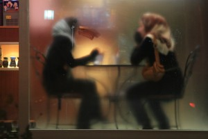 Two people wearing hijabs sit at a small table behind a foggy window