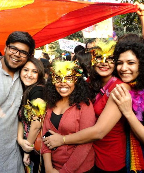 Five smiling people posing in front of a waving rainbow flag. Two are wearing gold masks with yellow feathers. Source: TARSHI