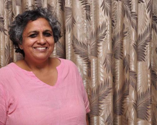 A photo of Anjali Gopalan, who has short black and gray hair and dark eyes. Anjali is smiling, wearing a light pink dupatta. Source: Naz Foundation