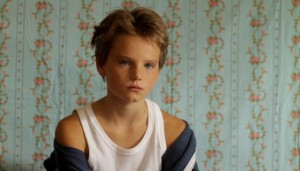 """A still from the movie """"Tomboy"""", showing a young child in a white vest and blue jacket that's falling off her shoulders."""