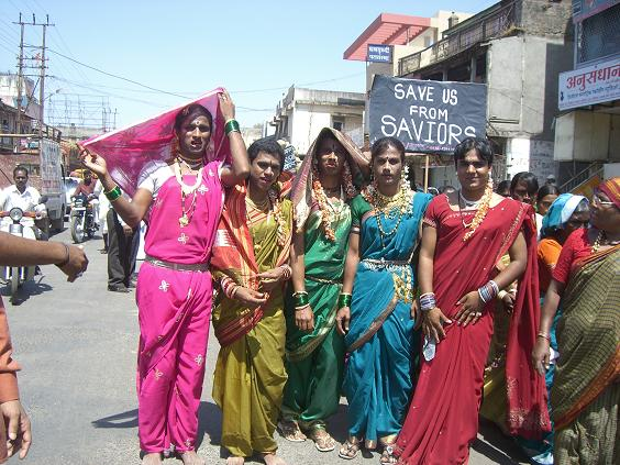 """Five transgender people walking down on an Indian road. Someone behind them is carrying a placard """"Save us from saviors"""". They are wearing bright-coloured sareers, gajras, bindis, and jewelery."""