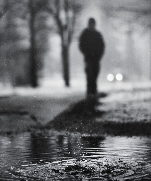A drop of water falls on a water body. A silhoutted figure in black-and-white is seen in the background.