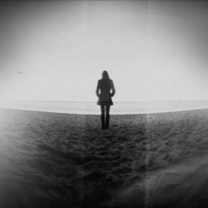 A black-and-white silhouette of a girl standing in a deserted wasteland