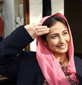 A still of actor Divya Dutta from the film 'Bhaag Milkha Bhaag'. She is wearing a pink headscarf and bloue jacket, and her right palm is held up to her head in the manner of a salute.