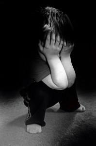 Black and white picture of a child covering their face