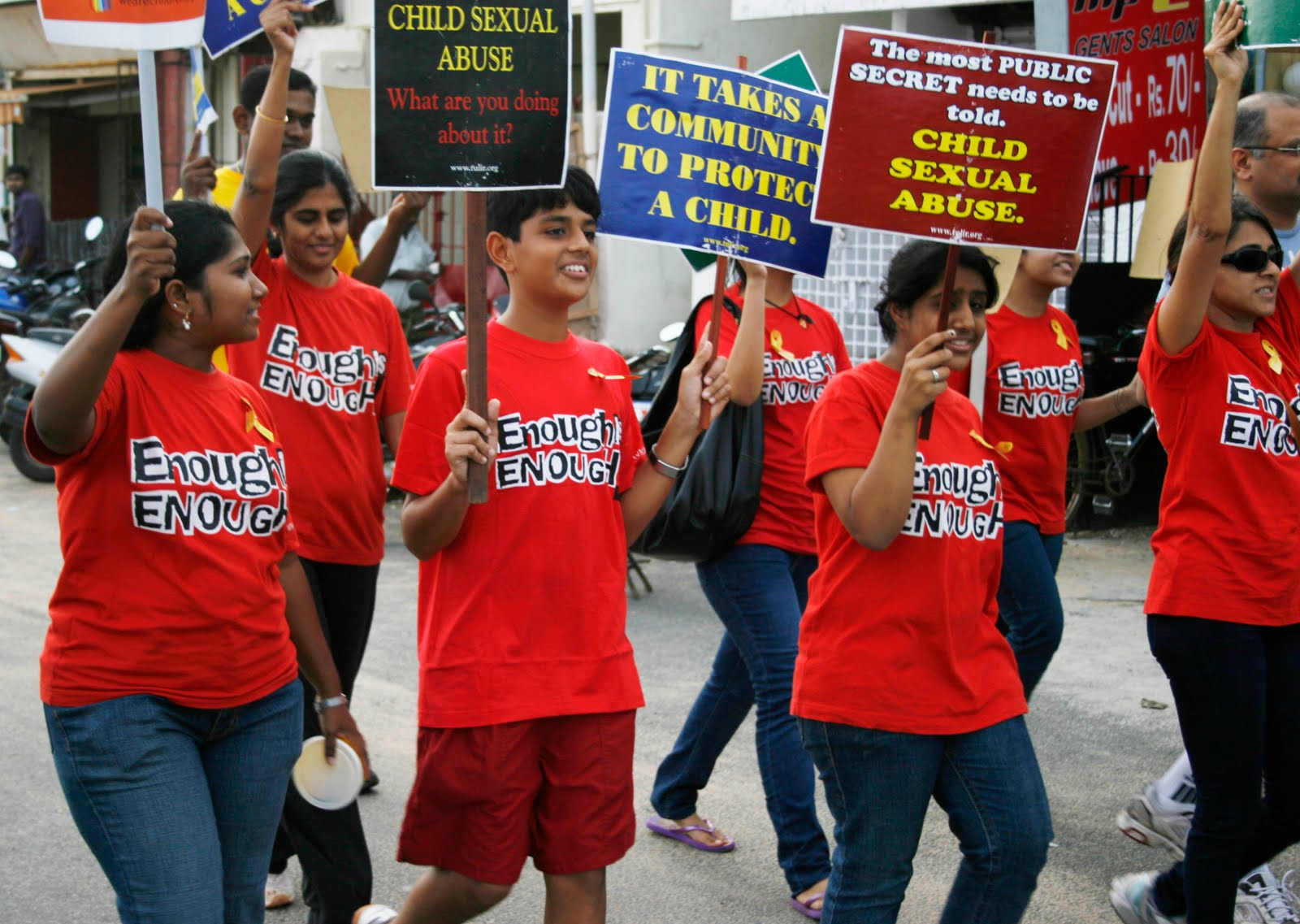 """Youngsters wearing red shirts with """"Enough is enough"""" written in black march on a road, carrying placards reading """"Child sexual abuse - what are you doing about it?""""; """"The most public secret needs to be told""""; and """"it takes a community to protect a child."""""""