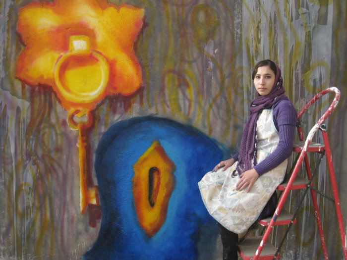 Picture of Afghani street artist Malina Suliman sitting in front of one of the street murals she has painted. She is wearing a white kurta with a purple cardigan and a purple headscarf.
