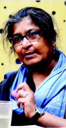 A picture of feminist scientist Chayanika Shah. Her hair is dark, with specks of grey. She has a blue scarf wrapped around her neck, and is wearing blue earrings.