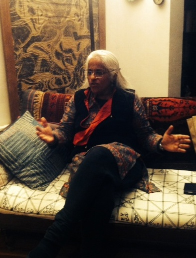 Picture of Maya Krishna Rao, seated in a couch with a cushion beside her. She has white hair and rimless glasses, her hands are spread out, almost like she is in the middle of explaining something.
