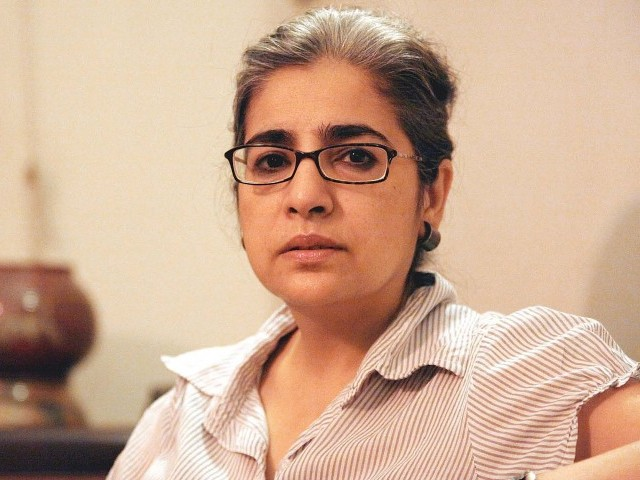 A picture of Pakistani feminist filmmaker Sabiha Sumar. Her dark hair has specks of gray in it, and she is wearing thick-rimmed glasses and a checked t shirt.