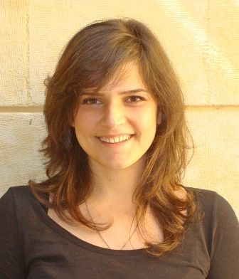 Photo of abortion activist Rola Yasmine. She has shoulder-length brown hair and fair skin. She is wearing a casual shirt.