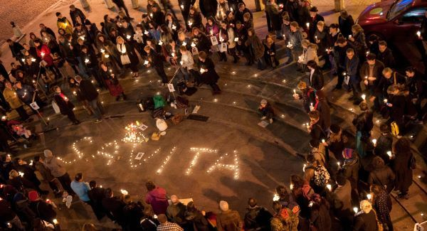 Photo of a candlelight vigil, showing a gathering of people coming together to write the name 'Savita' using candles