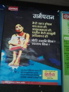 A poster for abortion rights in Nepal, showing a woman sitting with her legs pulled close to her chest. There is abortion-related information written beside her in hindi.
