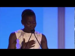 Photo of actress Lupita Nyongo speaking from a podium. She is wearing a white dress.