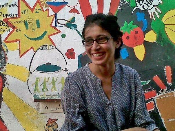 Photo of bodypositive activist Ekta Oza. She is wearing dark-rimmed glasses, a blue patterned kurta and her hair is tied back. She is looking to her left and laughing.