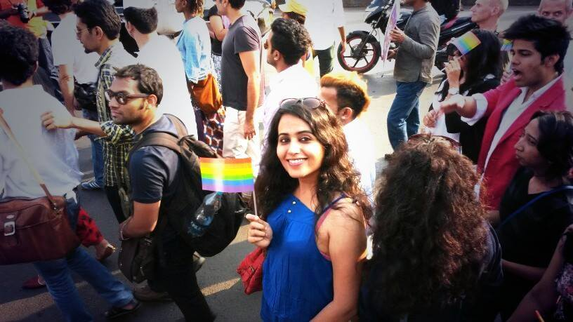 Photo of a woman in a pride parade, holding up a small queer pride flag