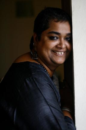 Photo of queer feminist activist Pramada Menon. She has short hair and is leaning against a wall. She is wearing a blue kurta, and a necklace.