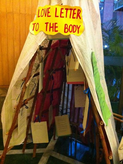 A tent-like structure which says 'love letter to the body' on top