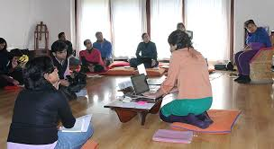 Picture of an ongoing workshop, where a woman sits in the middle with her laptop and there are people in the room sitting at various intervals around the woman and is listening to her talk.