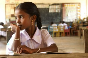 A picture of a girl child. She is wearing a pink frock and is staring to her left.