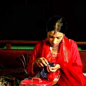 A young girl dressed in red looking downwards