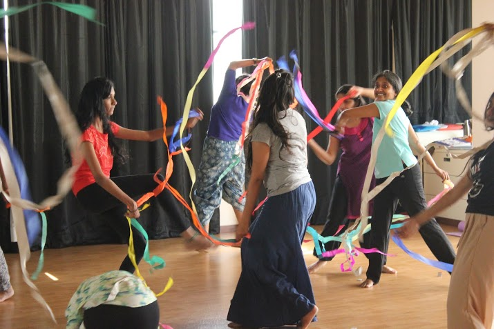 A group of women circling each other and dancing while waving colourful streamers.