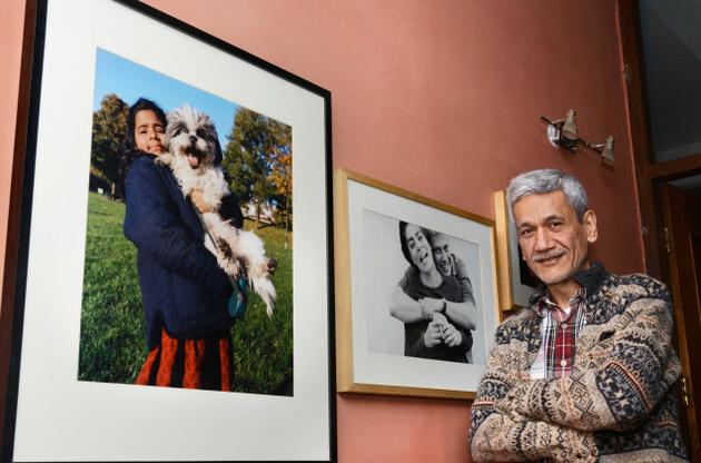 Artist Sunil Gupta stands infront of a wall which has two framed photos of his family. He has greying hair and is wearing a patterned woolen sweater.