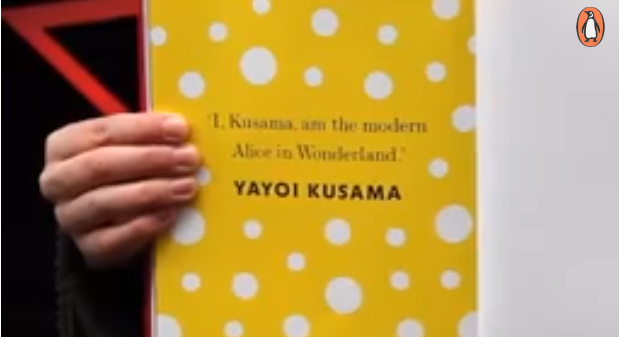 A hand holds up the cover of a book which reads, 'I, Kusama, am the modern Alice in Wonderland.'