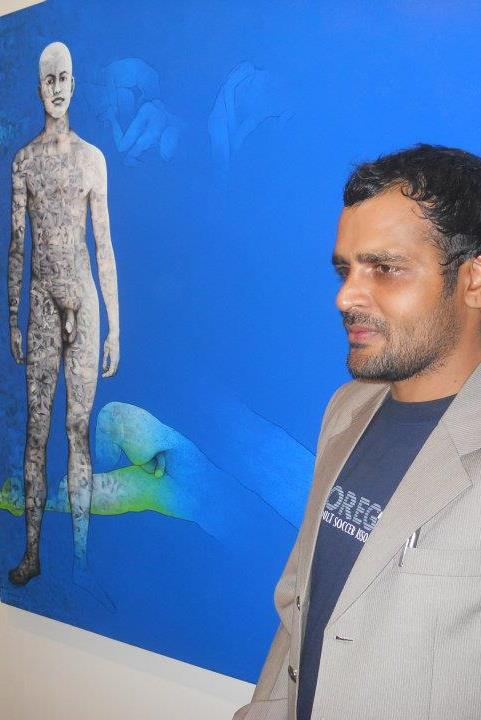 Photo of activist balbir krishan against a blue background. he is wearing a grey suit and has short black hair and a stubble