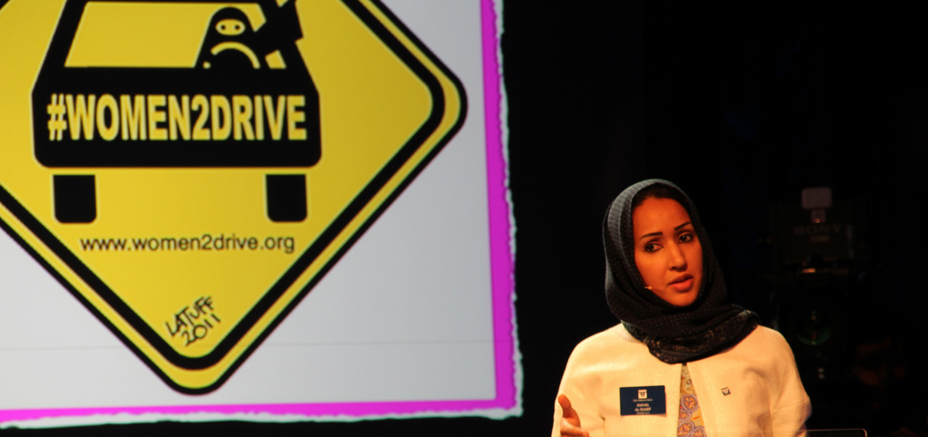 Photo of Saudi Arabian women's rights activist Manal Al Shairf. She has black hair and is wearing a black headscarf, and is standing in front of a board that says 'women2drive'.