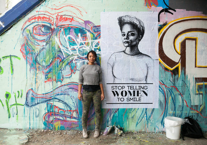 """Artist Tatyana Fazlalizadeh stands infront of a wall that has a mural painted on it. She has short hair and is wearing a simple top with trousers. There is also a poster behind her that says """"stop telling women to smile"""""""