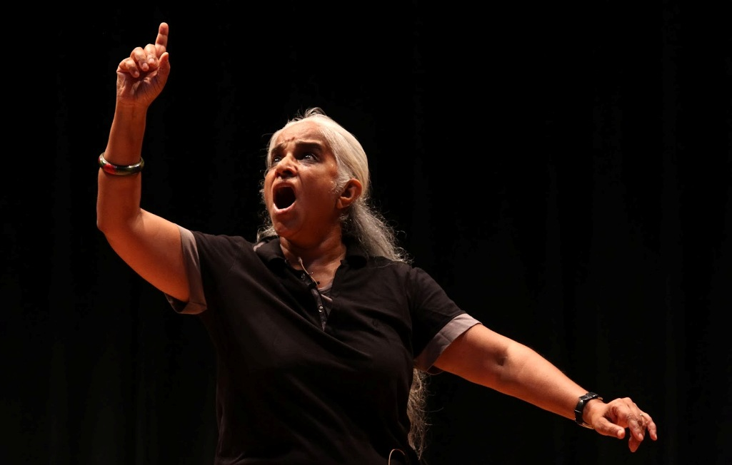 Photo of performance artist and theatre personality Maya Krishna Rao. She is wearing black and her left hand raised in a dramatic pose. She has long white hair and there is a red bindi on her forehead.