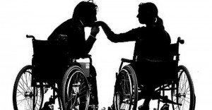 Silhouettes of a man and a woman sitting in two respective wheelchairs. The man is kissing the woman's hand