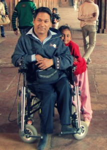 A man sits on a wheelchair. He's wearing a blue sweatshirt and blue trousers. A child in a bright pink sweater leans against his wheelchair