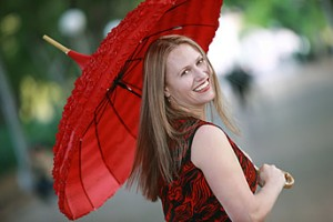 A woman dressed in a black and red dress and holding up a big red umbrella is looking behind. She has long blonde hair and a smile on her face.