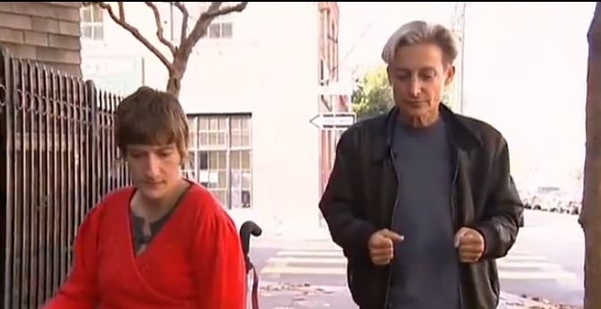feminist theorist judith butler, wearing a black shirt and trousers, walks beside wheelchair-bound disability rights activit sunnaura taylor, who's wearing a bright red top.