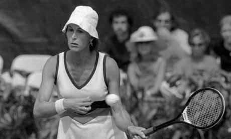A photo of Renee Richards, the first transsexual woman to play in competitive sport after transitioning. She is wearing a white uniform and cap and is holding up a tennis racket.