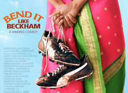 Poster for the film 'Bend It Like Beckham' showing a girl standing with her back facing the camera. She's wearing a cvolourful magenta and green sari and is holding sports shoes in her hands.