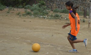 Picture of a girl playing football. She's wearing an orange jersey with purple sleeves and blue shorts. Her hair is tied back in a ponytail.