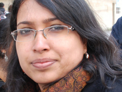photo of activist Dr. Payoshini Mitra. She wears glasses and long hair, and is wearing a black sweater with an orange-and-black patterned scarf