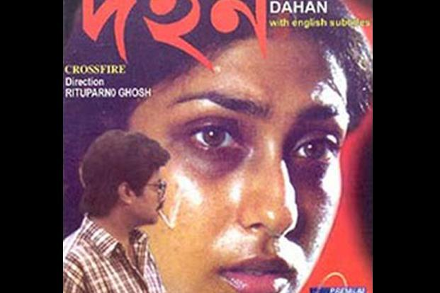 Poster for the Bengali film, 'Dahan', showing a woman's face enlarged and facing the camera, and the smaller figure of a man dressed in a chequered shirt looking at her