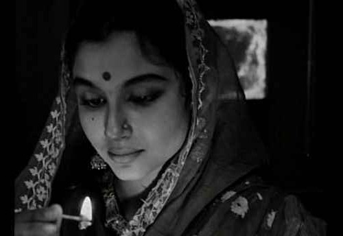 "A still from the film ""Apur Sansar"" showing a woman who's looking downwards. She's wearing a saree and her aanchal is draped around her head."