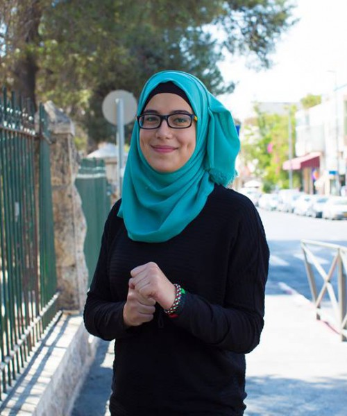 A woman dressed in a black sweater and a green hijab, wearing dark-rimmed glasses