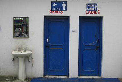 Two blue doors against a white wall, one having 'gents' and the othe rhaving 'ladies' written over it. beside them, there is a white sink.