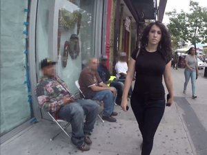 Photo of a woman walking down the street, she has curly hair and is wearing a black top and black pants