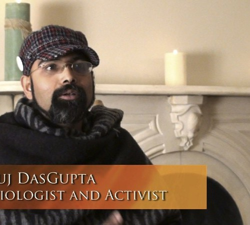Photo of gay activist Debanuj Dasgupta. He is wearing a brown sweater and cap, and has a thick beard.