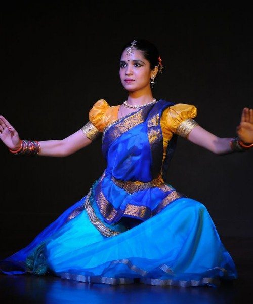 A woman wearing a blue saree and an orange blouse performing Kathak. She is wearing colourful bangles and jewellery on top of her forhead, ears, and neck. She is wearing kajal, a black bindi, and her hair is tied.