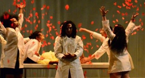 Stage performance of a few women in white coats holding down a woman on a table to commit Female Genital Mutilation, while others throw red rose pertals in air. One woman stands in the front and centre of the stage looking solemnly.